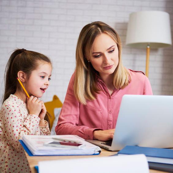 Mutter und Tochter sitzen vor Laptop. Daneben liegt ein Ordner.